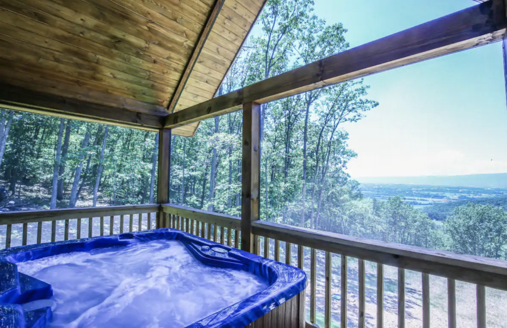 a hot tub on a deck with views over the valley below