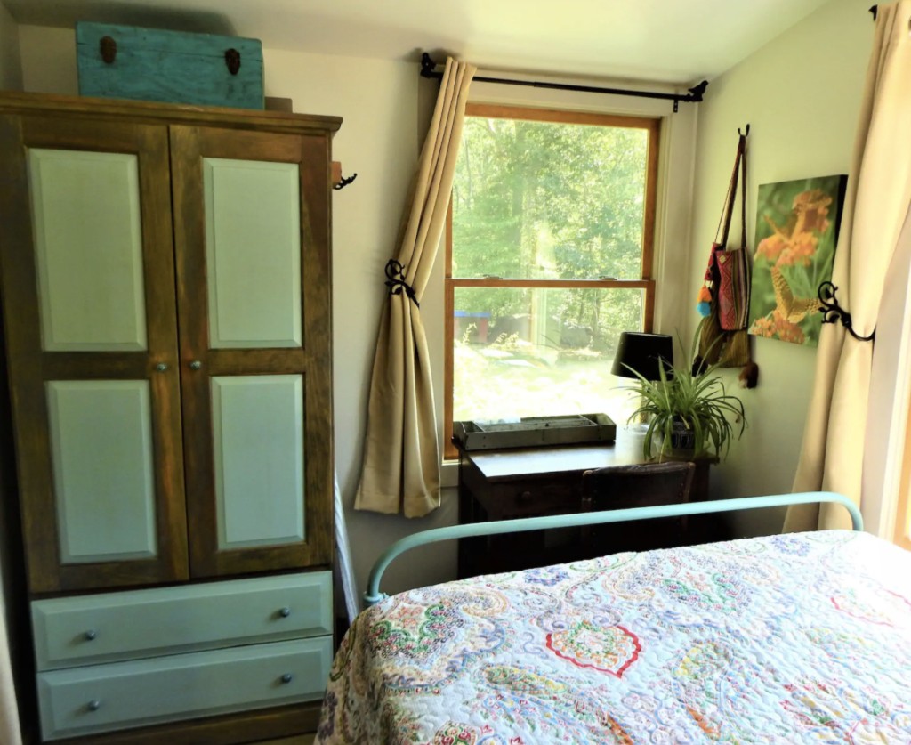 a bed with a quilt on it and a turquoise wardrobe