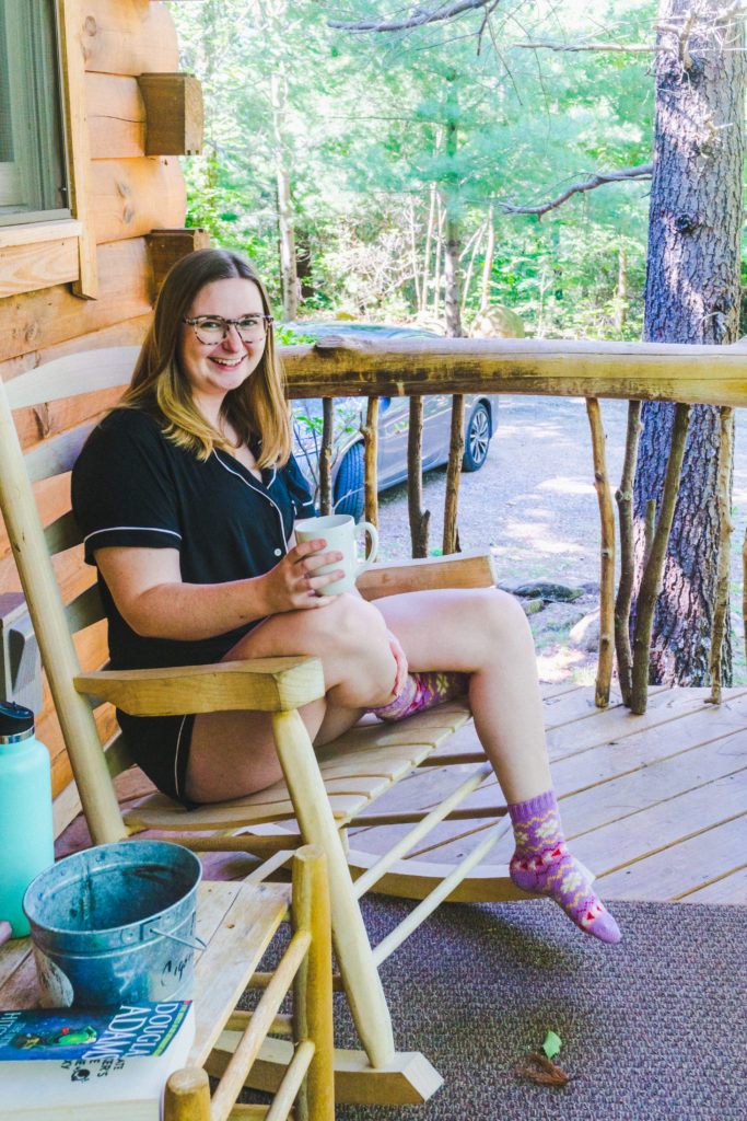 addie sitting on a wooden rocking chair with a cup of coffee